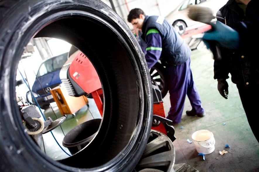 Unos mecánicos retiran neumáticos usados en un taller.