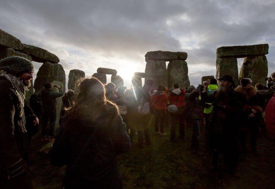 La gente se reúne en Stonehenge para ver el amanecer como parte de la ceremonia para ...