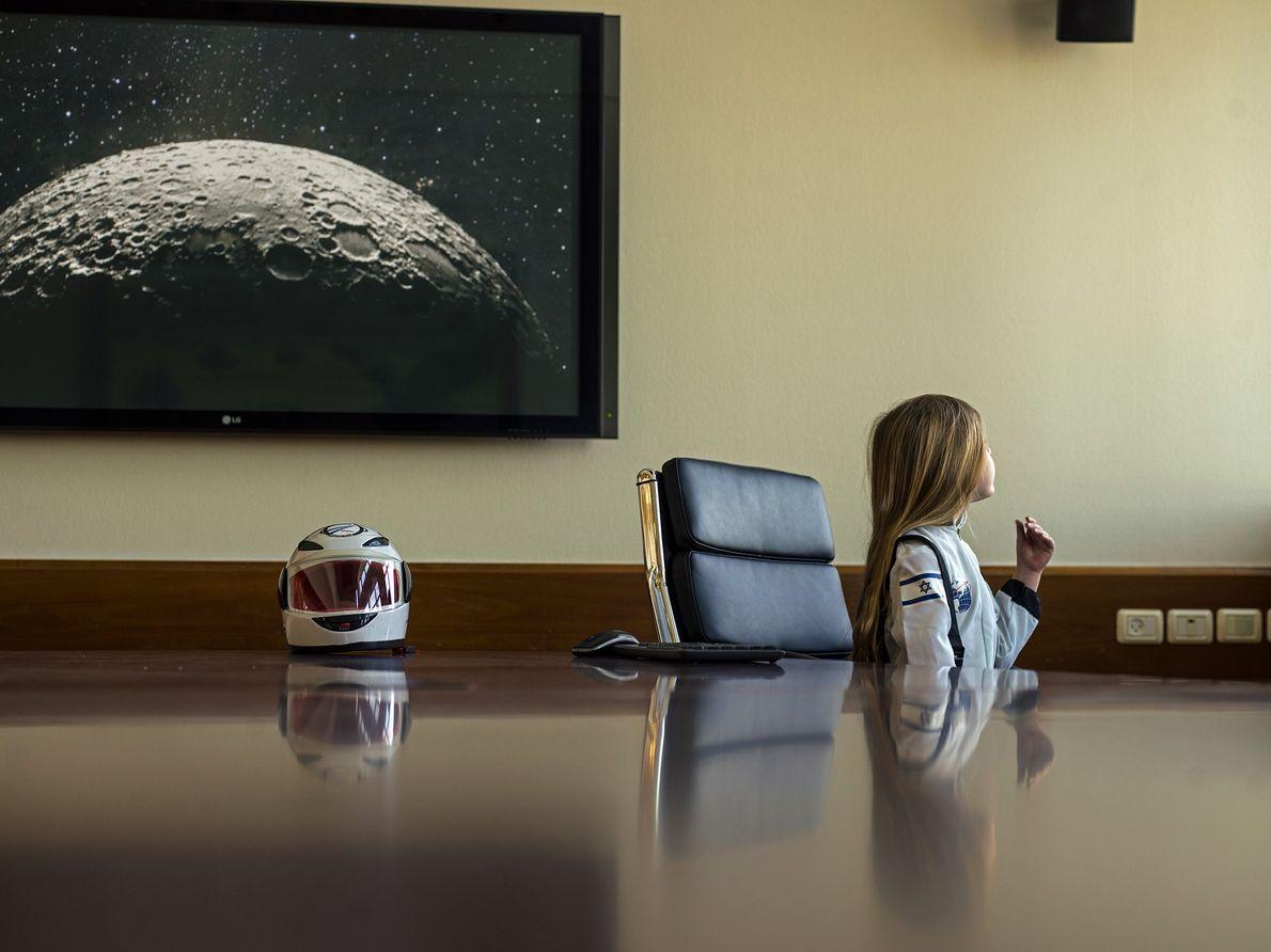 Una niña lleva su disfraz de astronauta oficial en la sede del equipo de SpaceIL en …