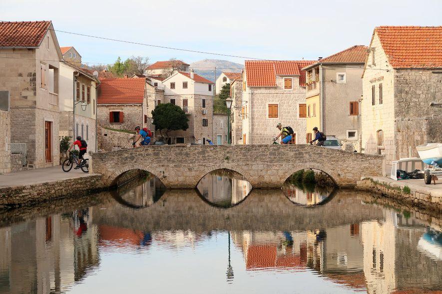 El Trans Dinárica permite a muchos visitantes pasar por primera vez por los lugares, aldeas y parques nacionales Patrimonio de la Humanidad de la Unesco. En esta foto, los ciclistas pasan por la aldea de Vrboska en la isla croata de Hvar.