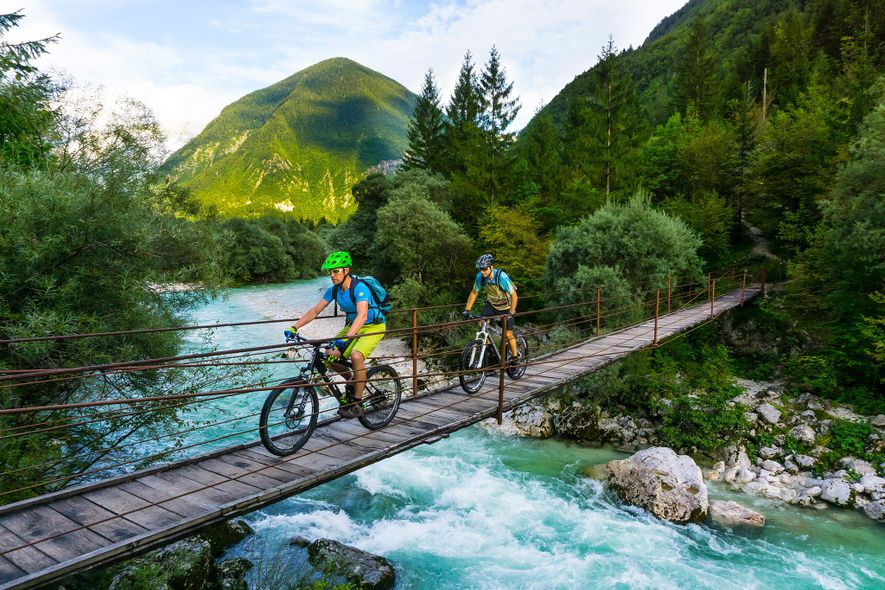 Unos ciclistas atraviesan un puente en el valle de Soča, Eslovenia.