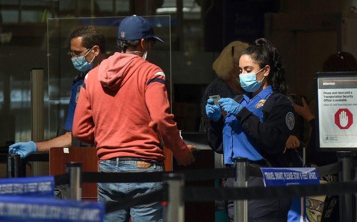 Agente de seguridad aeroportuaria comprueba el carné de un viajero