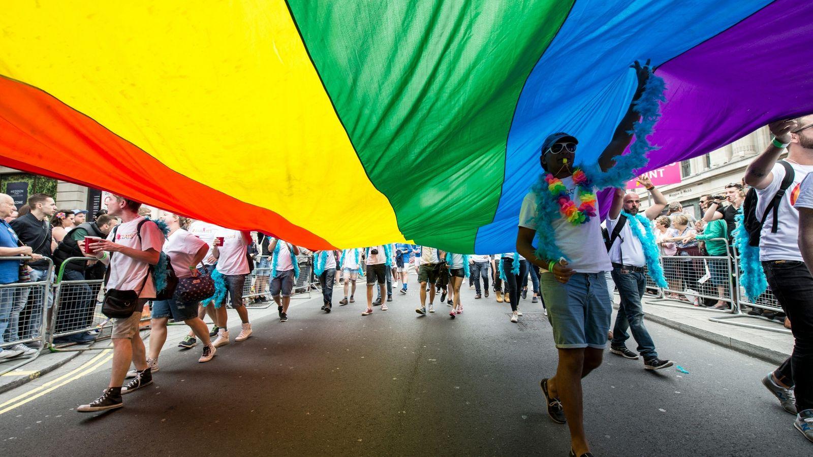 Manifestantes caminan con una bandera arcoíris gigante en Londres