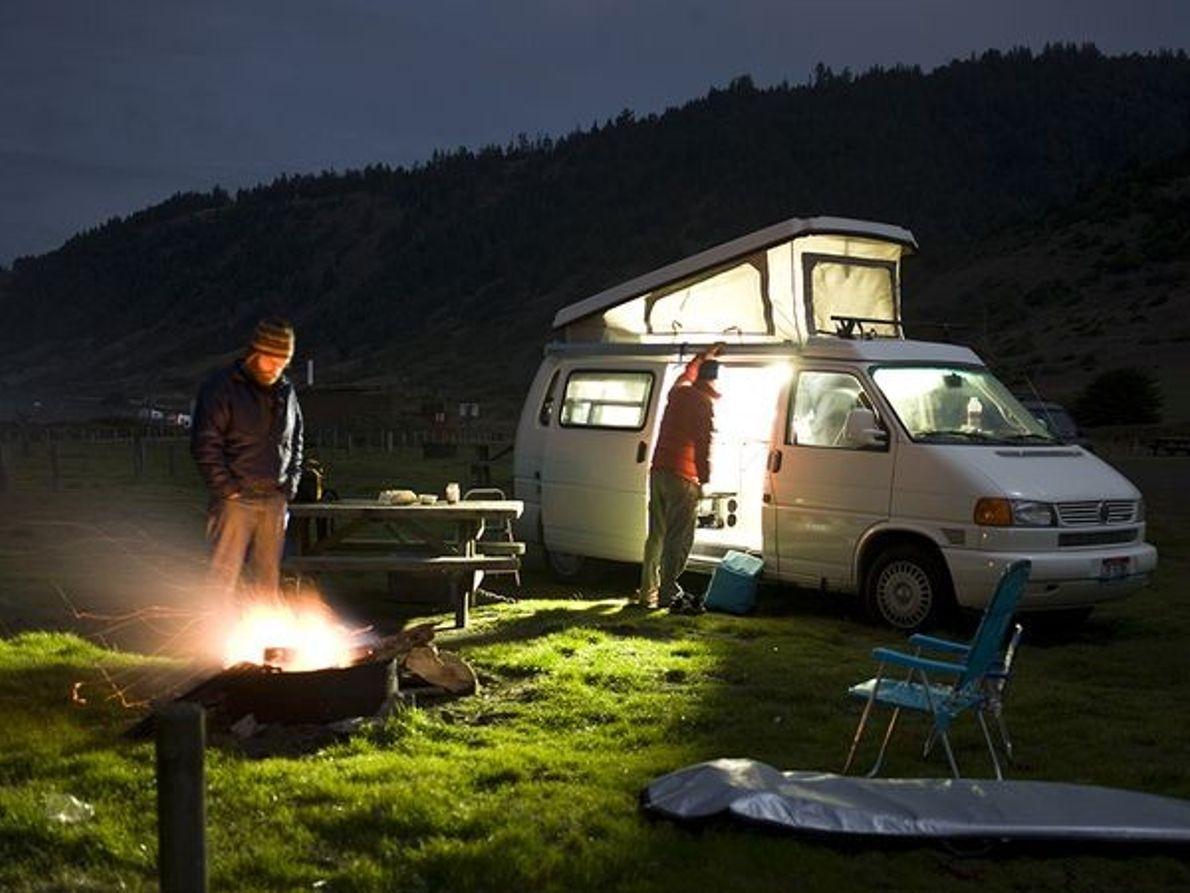 Imagen de personas acampando junto a su furgoneta.