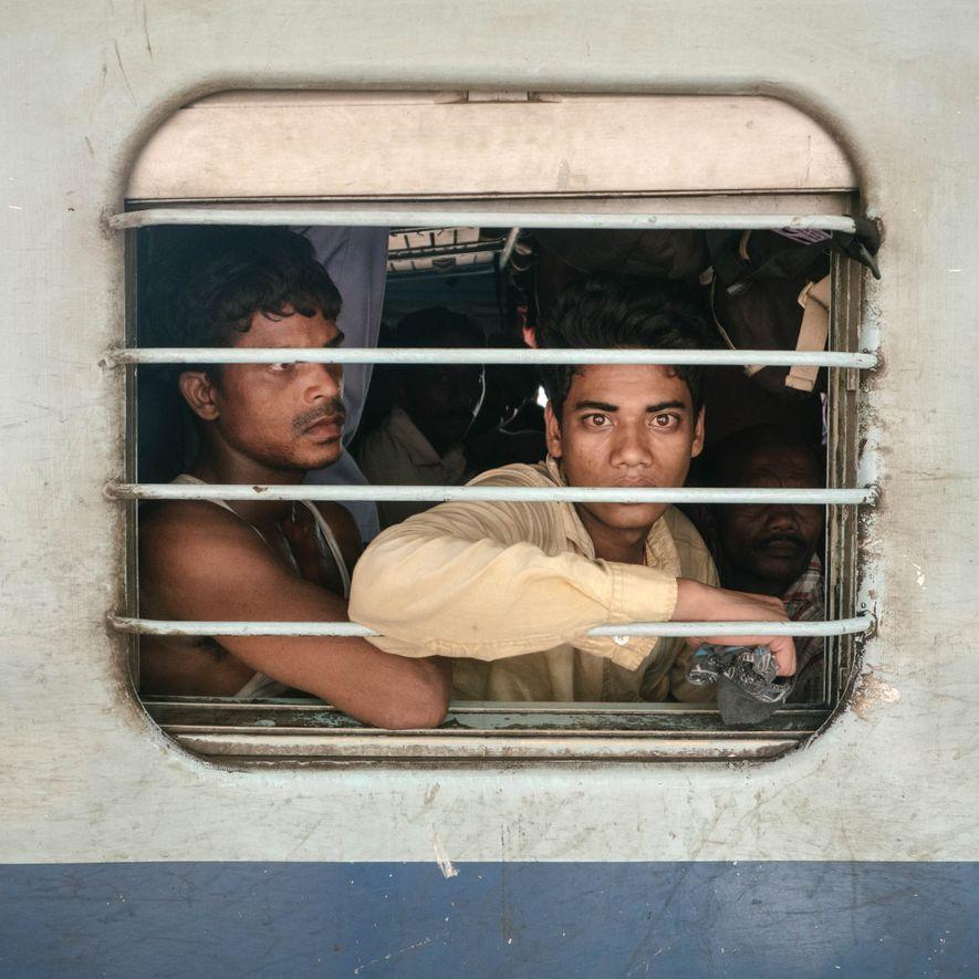 Los pasajeros miran por las ventanas del vagón de segunda clase. Muchos de ellos son trabajadores …