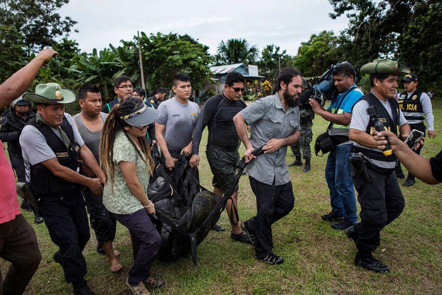 Las autoridades y los veterinarios transportan un manatí hasta un barco. El manatí estaba cautivo en un estanque para que los turistas le dieran de comer y se sacaran fotos con él.