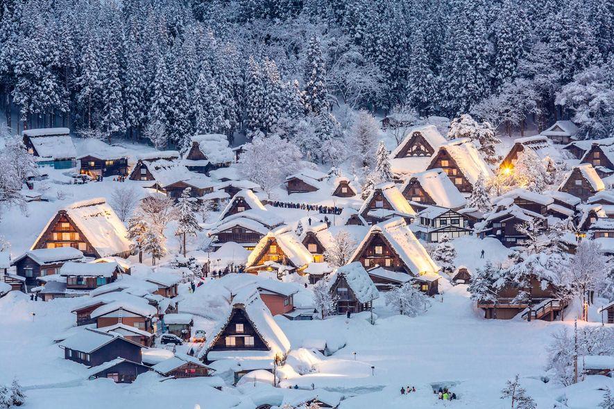 Las casas brillan cubiertas de nieve en Chubu, Japón. Este es uno de los muchos festivales ...