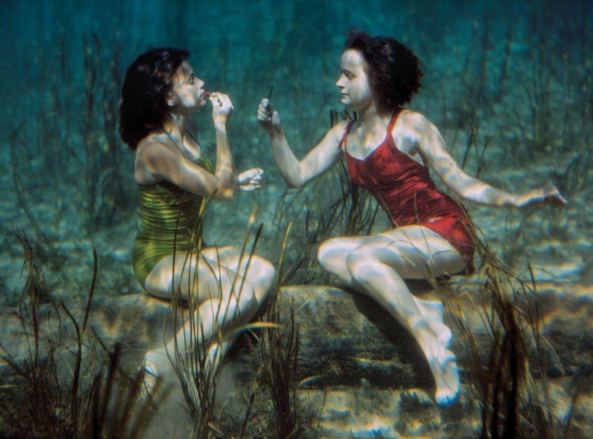 CIRCA 1944, FLORIDAUnas actrices que hacen de nadadoras se pintan los labios en las aguas cristalinas …