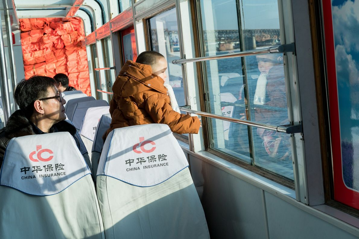 Padre e hijo viajan en barco por el río Yalu, que acerca a los turistas a …
