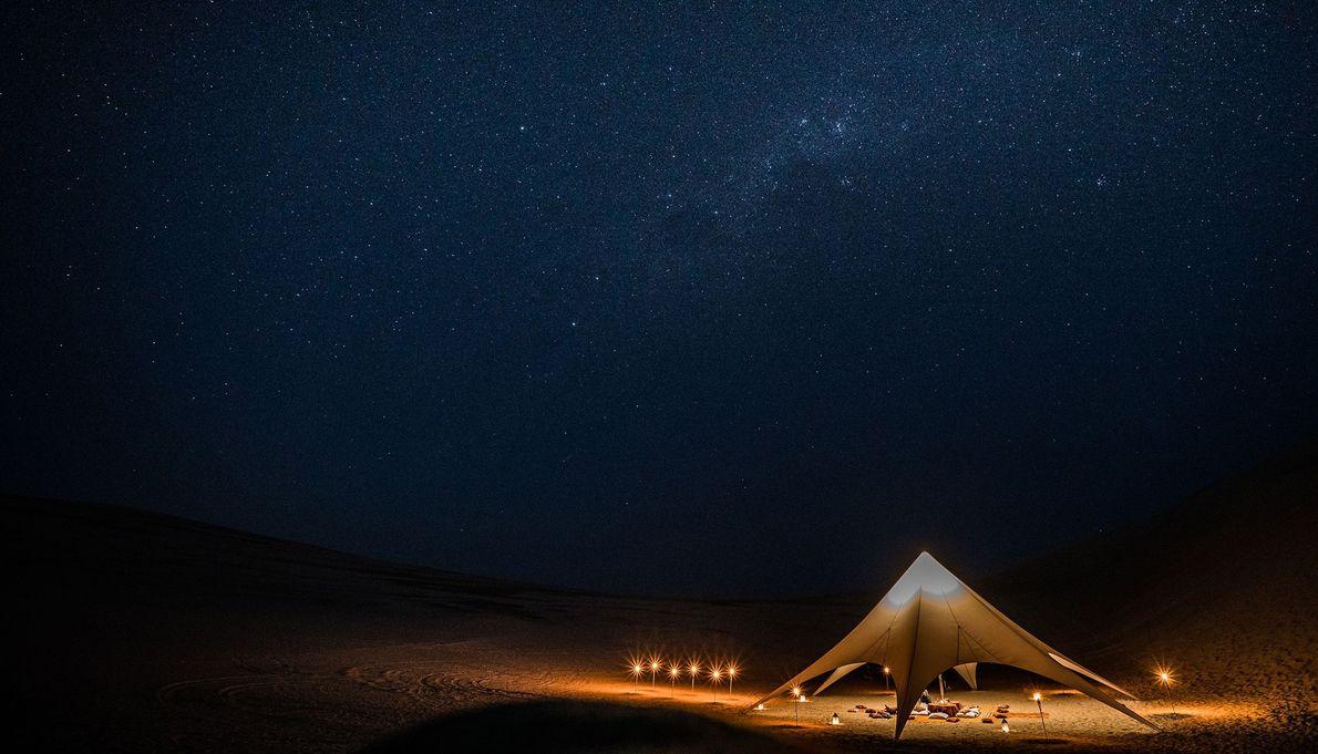 Una tienda iluminada en el desierto de Paracas, Perú.