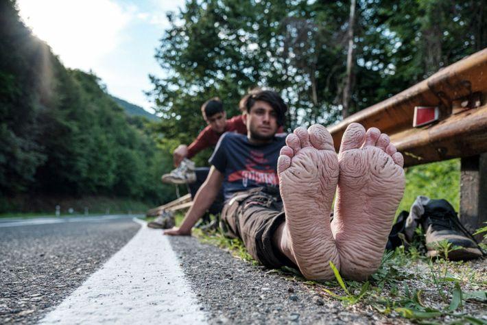 Jóvenes migrantes se airean los pies
